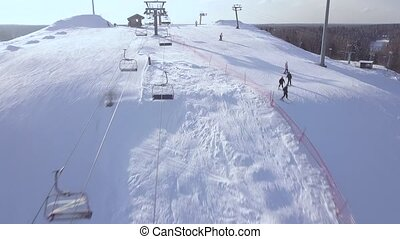 People skiing on snow slope on winter vacation at ski resort aerial view. Ski elevator fro skiing and snowboarding. Winter activity on snow mountain on drone view.