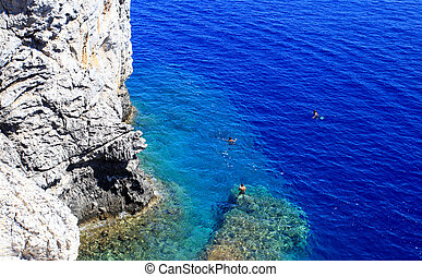 People snorkiling at a Secret cove Rhodes Greece - Crystal...
