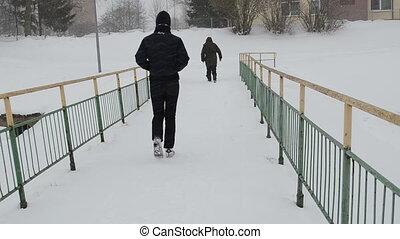 people snowstorm bridge