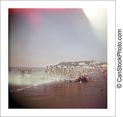 People spending the day at the beach. - A stock photograph...