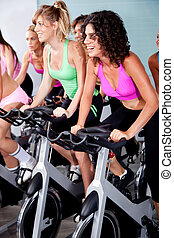 people spinning on bicycles in a gym
