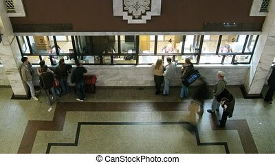 People stand at a ticket office