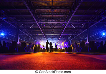 People stand, sit at table and look at illuminated stage in party; backs of people