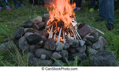 People standing around fireplace with burning wood flames