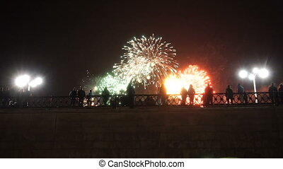 people standing on a bridge watching fireworks