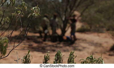 People standing under tree shade at Outback, NT - Medium...