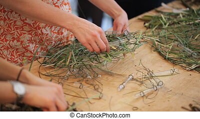 People stands near wooden table in art studio and create wreaths from grass.