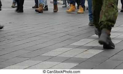 People step across a road by crosswalk or zebra crossing.