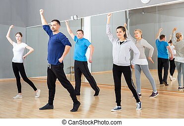 People stretching before dance training - Group of sporty ...
