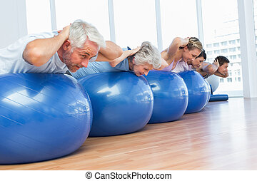People stretching on exercise balls in gym