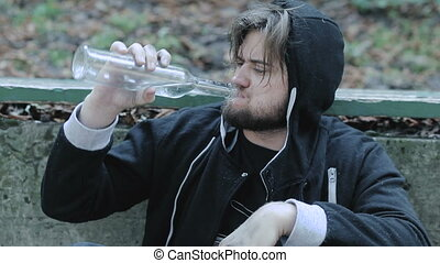 Portrait of young alcoholic, drunk man drinking vodka in...