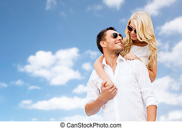 happy couple in sunglasses over blue sky
