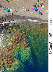 People sunbathe and swim on the pebble beach. Untouched nature,