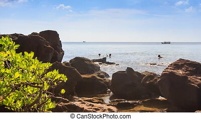 People Swim in Sea near Rock Beach Boats Drift past