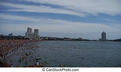People swim in sea,A lot of people at crowded bathing sandy beach.