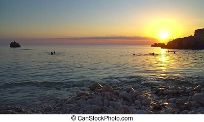 People Swim in the Sea at Sunset Time - Blue Bay beach on...