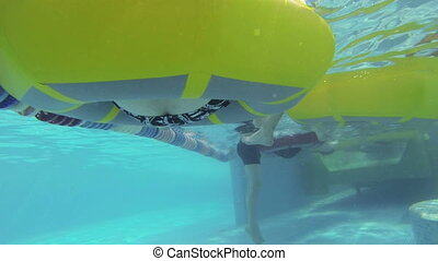 People swim on the inflatable circles in the water Park