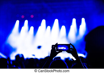 People taking photographs with touch smart phone at concert...