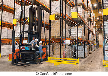 People talking by forklift truck in warehouse