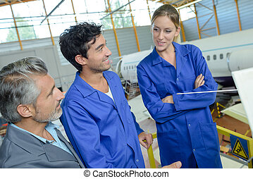 People talking in aircraft hangar