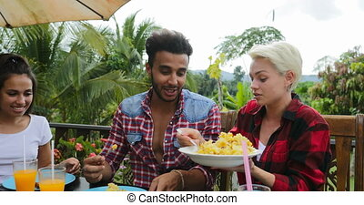 People Talking Passing Food Eating On Terrace Young Friends Sitting At Table Outdoors Laughing Communication