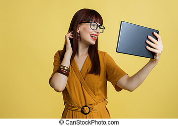 People, technologies, gadgets, lifestyle concept. Mock up copy space. Smiling attractive young woman in yellow dress, using tablet pc and smiling to her friend on video call, isolated on yellow