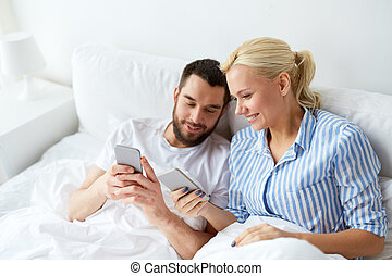 happy couple with smartphones in bed at home - people,...