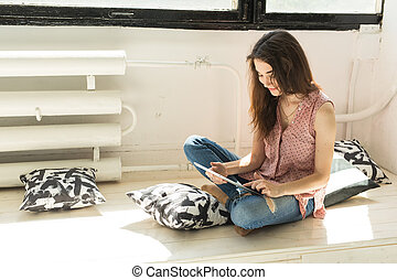 People, technology and interior concept - happy young woman sitting on the floor with tablet computer with pillows around