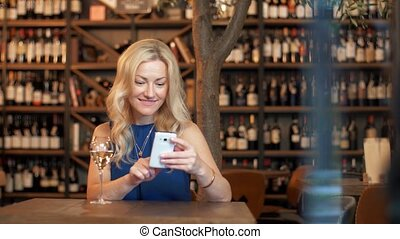 woman with smartphone at wine bar or restaurant