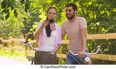 couple with bicycles taking selfie by smartphone - people,...