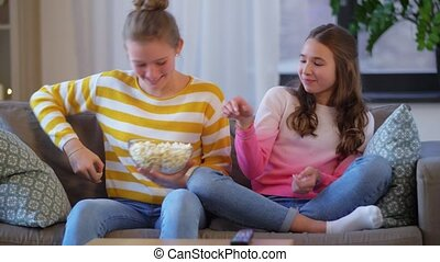 teenage girls eating popcorn at home - people, television ...
