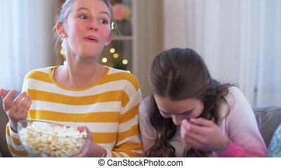 teenage girls eating popcorn at home - people, television ...
