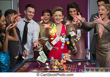People throwing chips and cash on roulette table in casino