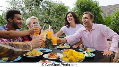 People Toasting Juice Glasses Sitting At Table On Terrace...