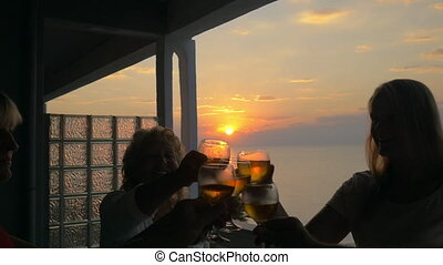 People toasting on the balcony at sunset