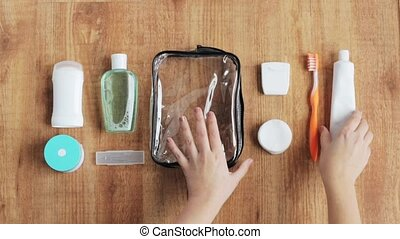 hands packing cosmetic bag for travel