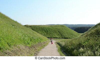 people tourist hill mound - tourist woman walk between mound...