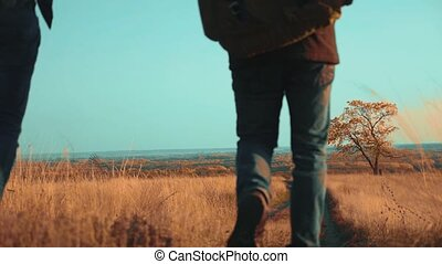 people tourists travel in lifestyle nature the autumn go on the road path adventure . slow motion video. two hiker with outdoor backpacks hiking. tourist concept the travel man tourism