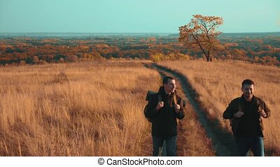 people tourists travel in nature lifestyle the autumn go on the road path adventure . slow motion video. two hiker with outdoor backpacks hiking. tourist concept the travel man tourism