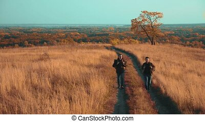 people tourists travel in nature the autumn go on lifestyle the road path adventure . slow motion video. two hiker with outdoor backpacks hiking. tourist concept the travel man tourism