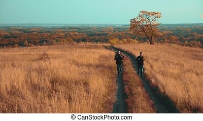 people tourists travel in nature the autumn go on the road path lifestyle adventure . slow motion video. two hiker with outdoor backpacks hiking. tourist concept the travel man tourism