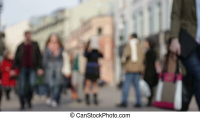 Unfocused figures of pedestrians walking through city street