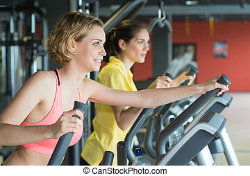 people training on machine in gym