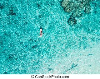 People traveling on kayak in transparent sea. Aerial view