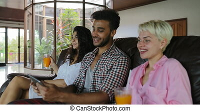 People Use Tablet Computer On Coach Watching Tv In Living Room Drink Juice, Young Man And Woman Group In Morning Talking Modern Apartment Interior
