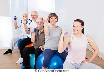 People Using Hand Weights While Sitting On Fitness Balls
