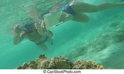 People Using Touch Pad Underwater - Slow motion shot of two...