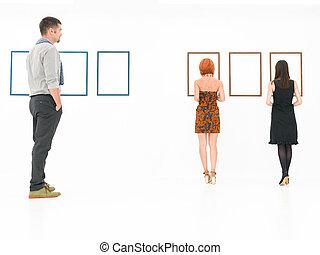 people visiting art museum - people in a white room looking...