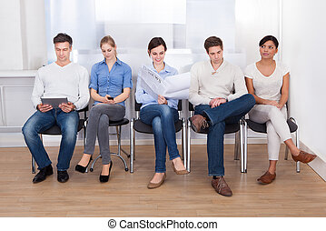 People Waiting In A Room - Group Of People Sitting On Chair...