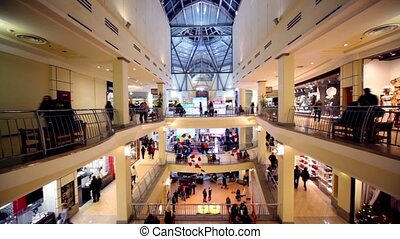 People walk along boutiques and other sit bench on multiple floors trade center